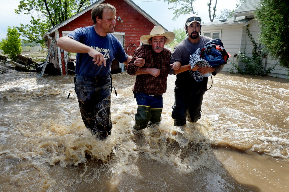 Description of . HYGIENE, CO. - SEPTEMBER 14:  Dan Hull, center, is assisted by Brian Marquedt, left, and Scott Johnson after rescuing Hull's two cats and gathering some items from his flooded home on Hygiene Road in Hygiene, CO September 14, 2013.  Covering the horrific flooding in September was exhausting for the entire staff- physically, mentally and emotionally. I felt fortunate to be witness to this scene- neighbors helping neighbors. When reporter Zahira Torres and I pulled onto Hygiene Road I was overwhelmed by the amount recovery efforts taking place despite the flood water still rushing through town. This community joining together confirmed my faith in humanity. (Photo By Craig F. Walker / The Denver Post)