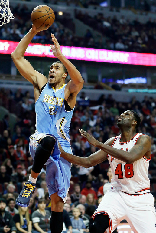 . Denver Nuggets center JaVale McGee, left, drives to the basket past Chicago Bulls center Nazr Mohammed during the first half of an NBA preseason basketball game in Chicago on Friday, Oct. 25, 2013. (AP Photo/Nam Y. Huh)