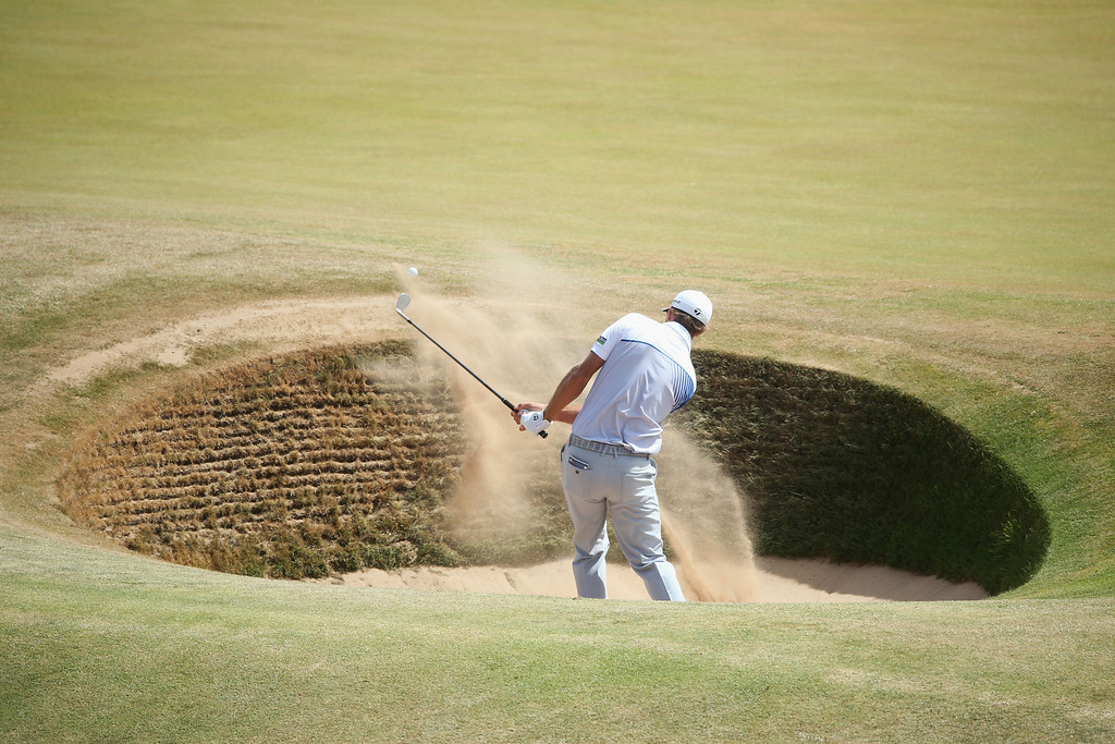 . Dustin Johnson of the United States hits out of the bunker on the 4th hole during the final round of the 142nd Open Championship at Muirfield on July 21, 2013 in Gullane, Scotland.  (Photo by Andrew Redington/Getty Images)