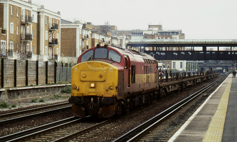 """-- 2004 -- A work worn #37682, """"Hartlepool Pipe Mill""""; heads north through Kensington Olmypia with a long rake of empty steel coil carriers. Put into store at Toton Depot two days later she was eventually withdrawn in August 2007 before being sold to Harry Needle Rail Ltd three months later who restored it before selling it on to Direct Rail Services (DRS) in September 2008."""