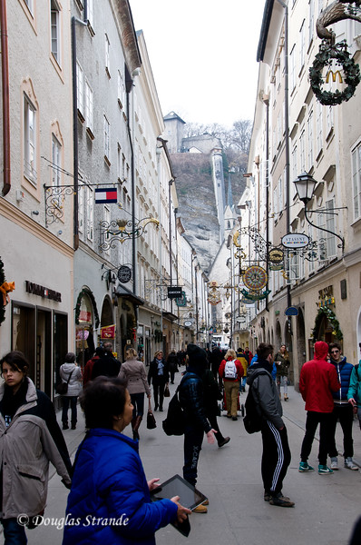 Busy shopping street in Salzburg.  Funincular on the distant hillside.