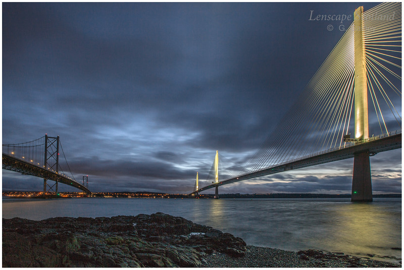 Forth Road Bridge and Queensferry Crossing from the shore at North Queensferry