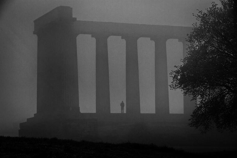 Lone figure on Calton Hill in Edinburgh in a typical Scottish fog