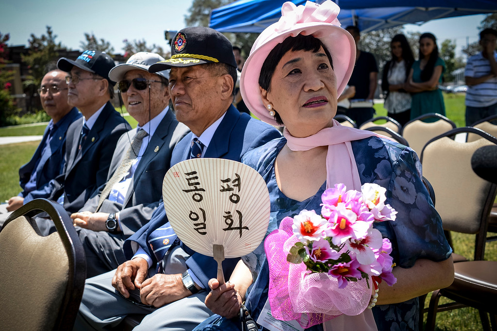 ". Poklim Kim of Los Angeles holds a fan asking for peace and unification at the unveiling of a statue honoring the ""comfort women\"" of WWII in Glendale Tuesday.  The statue honors the victims of military sexual slavery during the war.   Photo by David Crane/Staff Photographer"