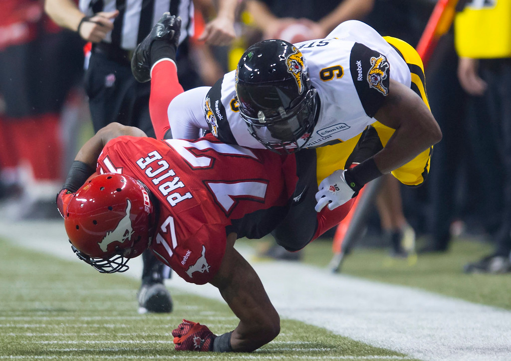 . Hamilton Tiger-Cats defensive back Brandon Stewart (9) tackles Calgary Stampeders wide receiver Maurice Price (17) during the first half of the CFL Grey Cup championship football game in Vancouver, British Columbia, Sunday, Nov. 30, 2014. (AP Photo/The Canadian Press, Nathan Denette)