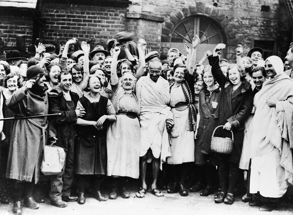 . Indian nationalist leader Mahatma Gandhi (Mohandas Karamchand Gandhi, 1869 - 1948) is greeted by a crowd of  female textile workers during a visit to Darwen, Lancashire, 1931.(Photo by Keystone/Getty Images)