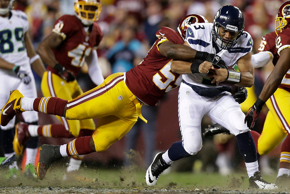 Description of . Seattle Seahawks quarterback Russell Wilson is stopped by Washington Redskins inside linebacker London Fletcher during the first half of an NFL wild card playoff football game in Landover, Md., Sunday, Jan. 6, 2013. (AP Photo/Evan Vucci)