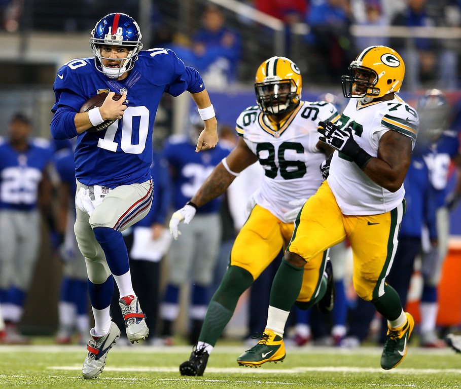 . Eli Manning #10 of the New York Giants carries the ball as  Mike Daniels #76 and  Mike Neal #96 of the Green Bay Packers defend at MetLife Stadium on November 17, 2013 in East Rutherford, New Jersey.The run by Manning was called back after a penalty against the New York Giants.  (Photo by Elsa/Getty Images)