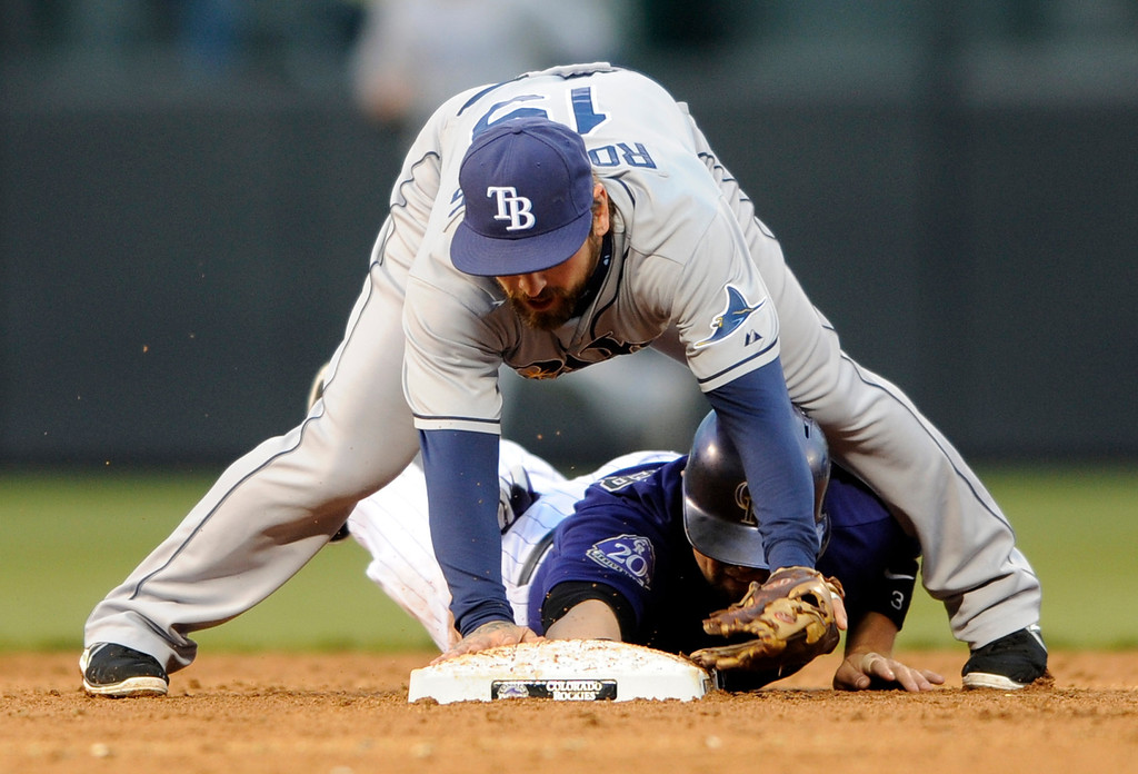 . Tampa Bay Rays second baseman Ryan Roberts (19) straddles Colorado Rockies\' Michael Cuddyer (3) after forcing him out during the third inning of a baseball game Saturday, May 4, 2013, in Denver. (AP Photo/Jack Dempsey)