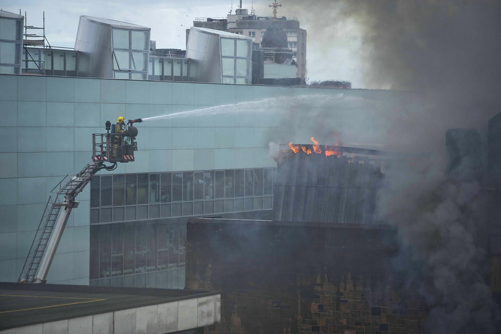 . A firefighter tackles a blaze at the Glasgow School of Art Charles Rennie Mackintosh Building on May 23, 2014 in Glasgow, Scotland. The fire at the A-listed building is said to have started in the basement after a projector exploded. The school has stated that all students and staff were evacuated safely.  (Photo by Chris Watt/Getty Images)
