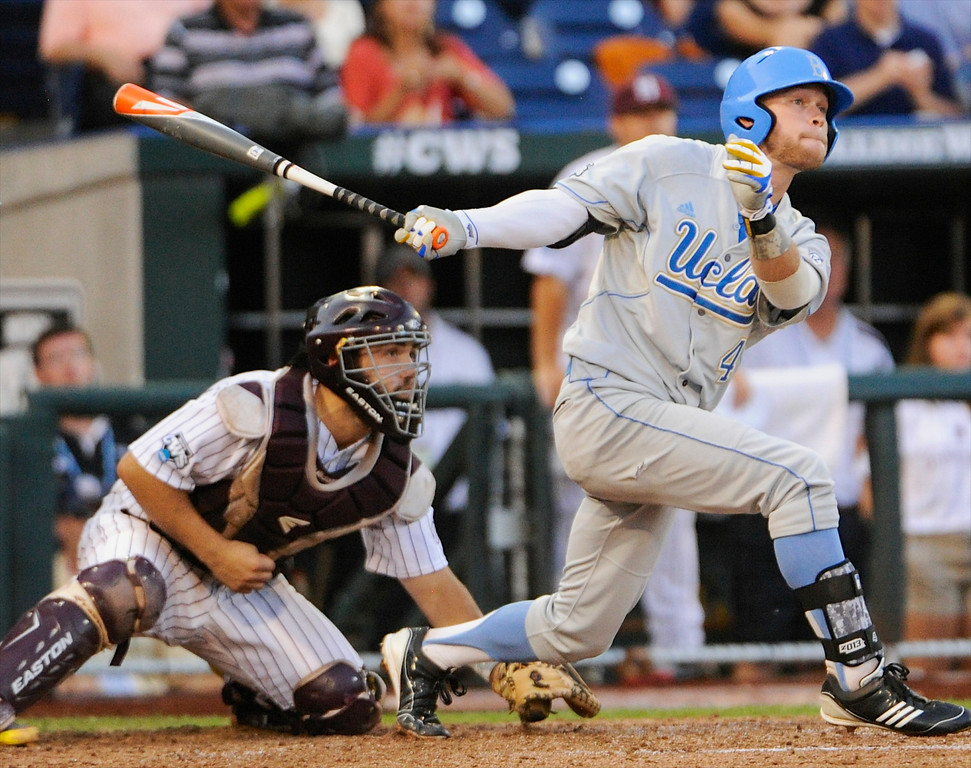 . UCLA\'s Eric Filia follows his two-RBI single to right field with Mississippi State catcher Nick Ammirati, left, in the fourth inning of Game 1 in their NCAA College World Series baseball finals, Monday, June 24, 2013, in Omaha, Neb. UCLA\'s Brian Carroll and Brenton Allen scored on the play. (AP Photo/Francis Gardler)