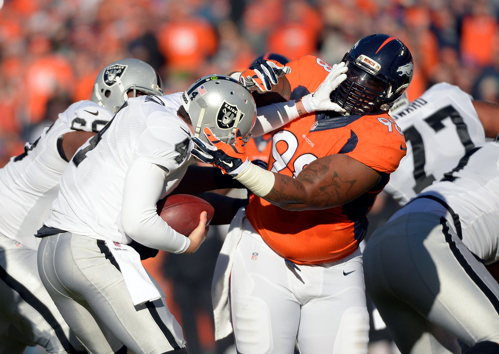 . DENVER, CO - DECEMBER 28: Derek Carr (4) of the Oakland Raiders pushes away Terrance Knighton (98) of the Denver Broncos and is sacked later on the play by Von Miller (58) of the Denver Broncos in the first quarter.  The Denver Broncos played the Oakland Raiders at Sports Authority Field at Mile High in Denver on December, 28 2014. (Photo by Joe Amon/The Denver Post)