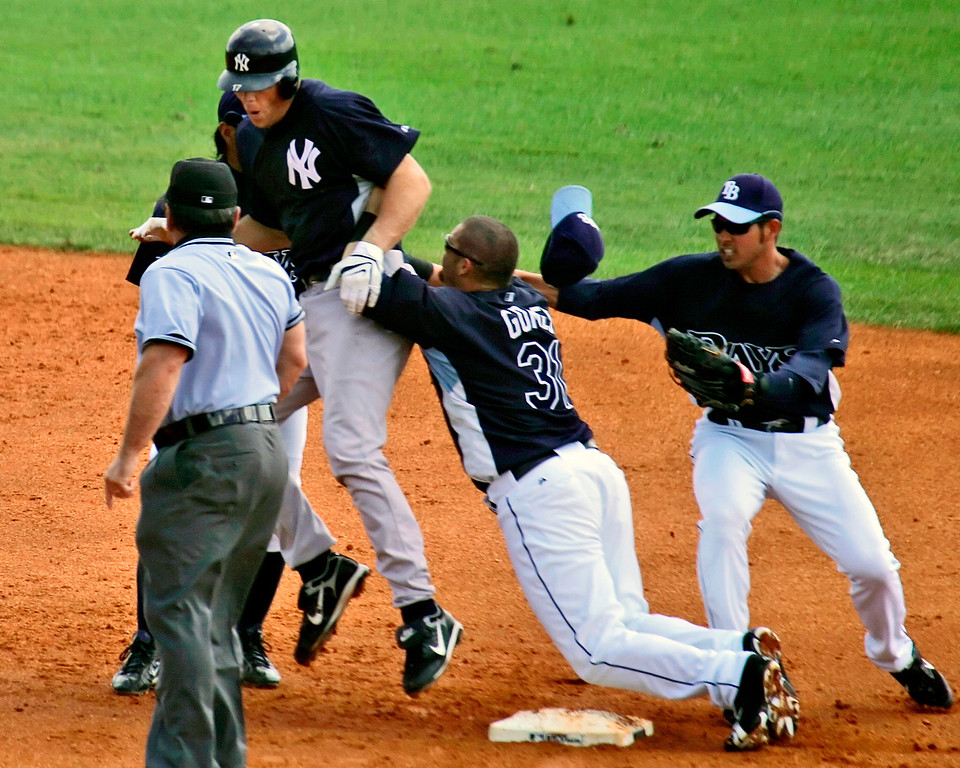 . Tampa Bay Rays right fielder Jonny Gomes, center, plows into New York Yankees\' Shelley Duncan to begin a second inning bench clearing brawl iduring spring baseball action in St. Petersburg, Fla.,  Wednesday, March 12, 2008. At left is umpire Charlie Reliford, at left is Rays shortstop Jason Bartlett. (AP Photo/Gene J. Puskar)