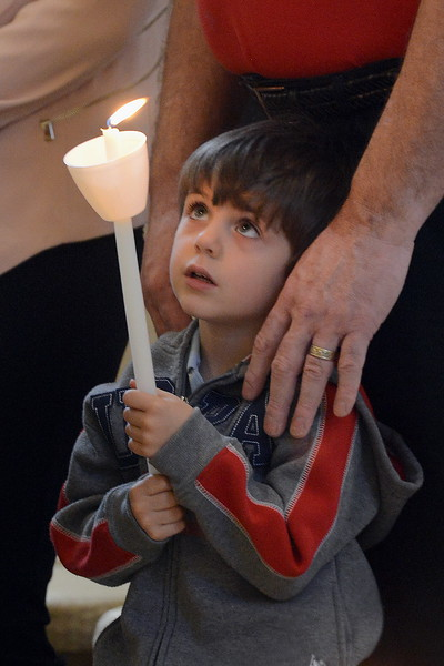 Bob Donaldson/Post-Gazette. 20150412. Orthodox Easter. Standalone. Local. Rev. Fr. John Touloumes lights the candles of parishioners begin the Paschal Vespers service Sunday morning at Holy Trinity Greek Orthodox Church in McCandless. Because Orthodox churches follow the Julian calendar, their Easter falls week after most Christian denominations. Writer: Standalone. Story Slug: unknown