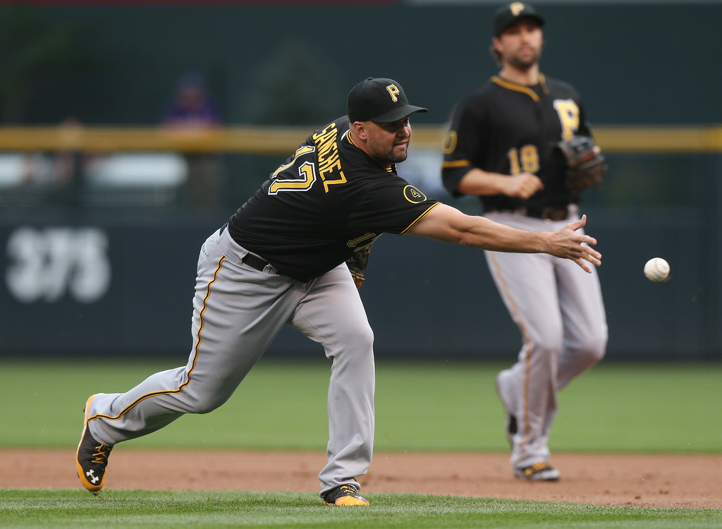 . Pittsburgh Pirates first baseman Gaby Sanchez, front, throws to first base after fielding bunt by Colorado Rockies leadoff hitter Charlie Blackmon in the first inning of a baseball game in Denver on Saturday, July 26, 2014. Blackmon was safe on the play. Pirates second baseman Neil Walker covers at back. (AP Photo/David Zalubowski)
