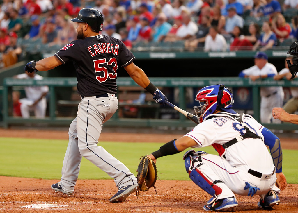 . Cleveland Indians\' Melky Cabrera (53) follows through on a double in front of Texas Rangers catcher Robinson Chirinos, right, during the fifth inning of a baseball game, Saturday, July 21, 2018, in Arlington, Texas. (AP Photo/Jim Cowsert)