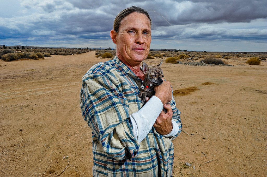 . Hinkley resident Lynette Morris, 55, and her three-month-old Teacup Chiwawa Trixie stand in front of the rural desert landscape in Hinkley, Calif. on Thursday, March 7, 2013. Morris has lived in Hinkley for nearly 10 years and is raising four grandkids in the town. (Rachel Luna / San Bernardino Sun)