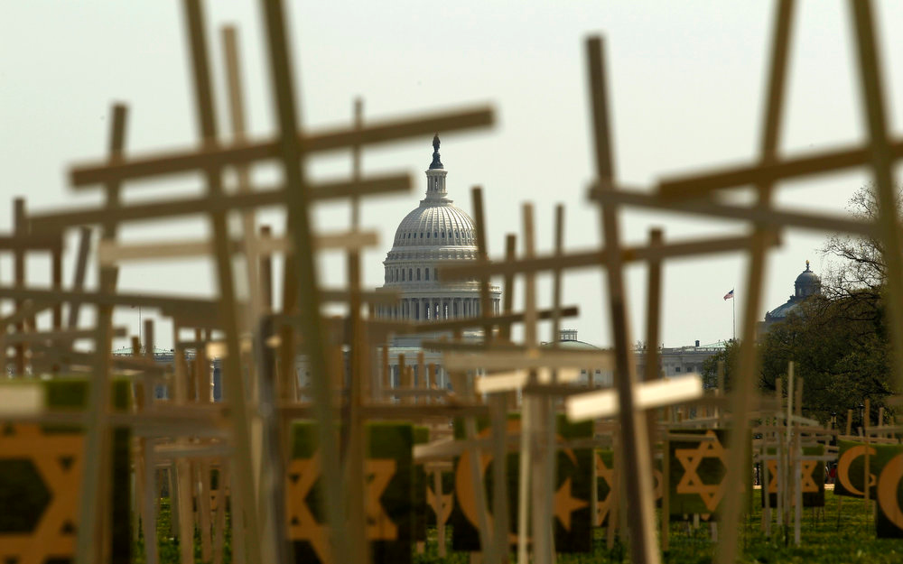 "Description of . With the U.S. Capitol in the background, crosses symbolizing grave markers are placed upon the National Mall in Washington April 11, 2013. The PICO National Network\'s Lifelines to Healing and Sojourners are holding a 24-hour vigil featuring a gathering of Newtown clergy and 3,300 grave markers to ""remind Congress action is needed on gun violence prevention\"". The number 3,300 represents the supposed number of people who have died as a result of gun violence since the tragedy in Newtown.  REUTERS/Kevin Lamarque"