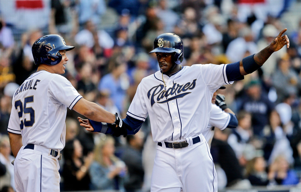 . San Diego Padres\' Cameron Maybin is congratulated by Will Venable after scoring on a double by Mark Kotsay against the Los Angeles Dodgers in the seventh inning of a baseball game in San Diego, Tuesday, April 9, 2013. (AP Photo/Lenny Ignelzi)