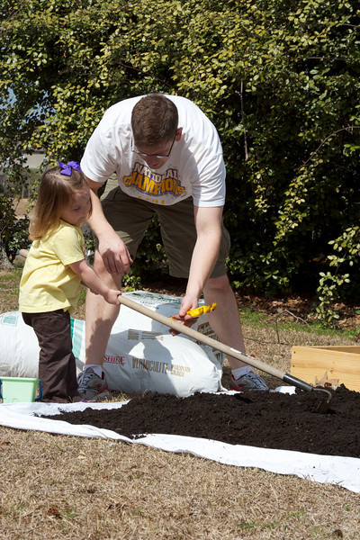 Brian showing Anna how to mix the soil