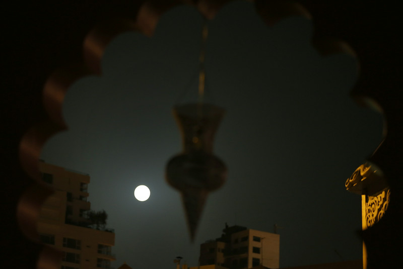 ". A perigee moon, also known as a supermoon, is seen behind a lantern, used as decoration during the Muslim holy month of Ramadan, decorating a building in Beirut, Lebanon, Saturday, July 12, 2014. The phenomenon, which scientists call a ""perigee moon,\"" occurs when the moon is near the horizon and appears larger and brighter than other full moons. (AP Photo/Hussein Malla)"