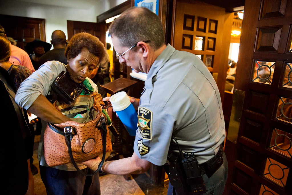 . A parishioner has her bag checked by a sheriff\'s deputy before entering a prayer vigil at Morris Brown AME Church for the people killed Wednesday night during a prayer meeting inside Emanuel AME Church in Charleston, S.C., Thursday, June 18, 2015. (AP Photo/David Goldman)