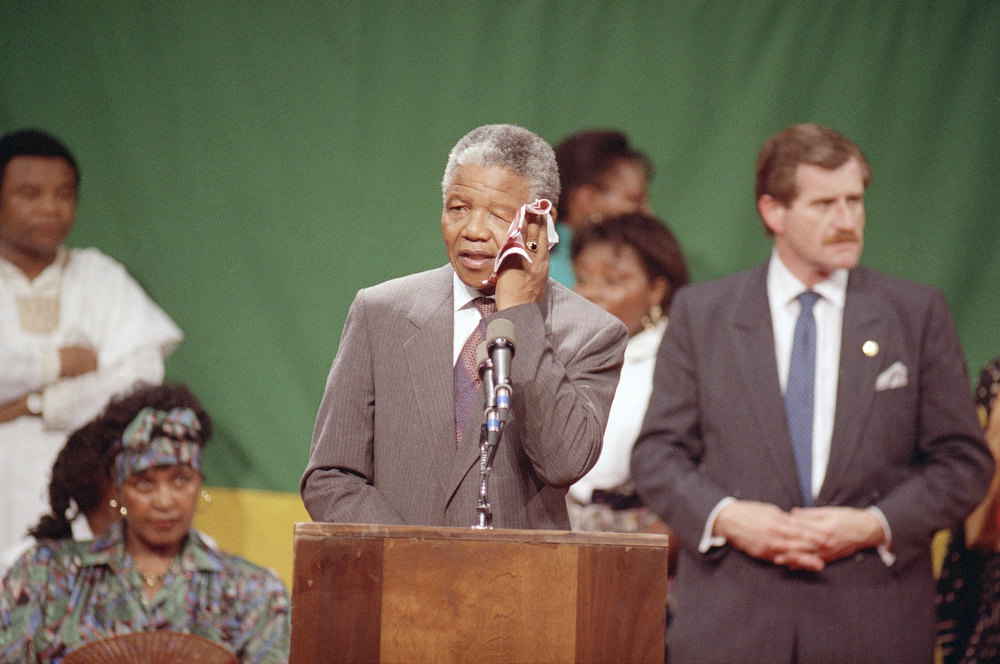 Description of . Nelson Mandela, deputy president of the African National Congress, wipes his brow in the hot, humid gymnasium of the Madison Park High School in the Roxbury section of Boston Saturday, June 23, 1990.   An exhuberant crowd packed the gymnasium for Mandela's appearance. (AP Photo/Jim Gerberich)
