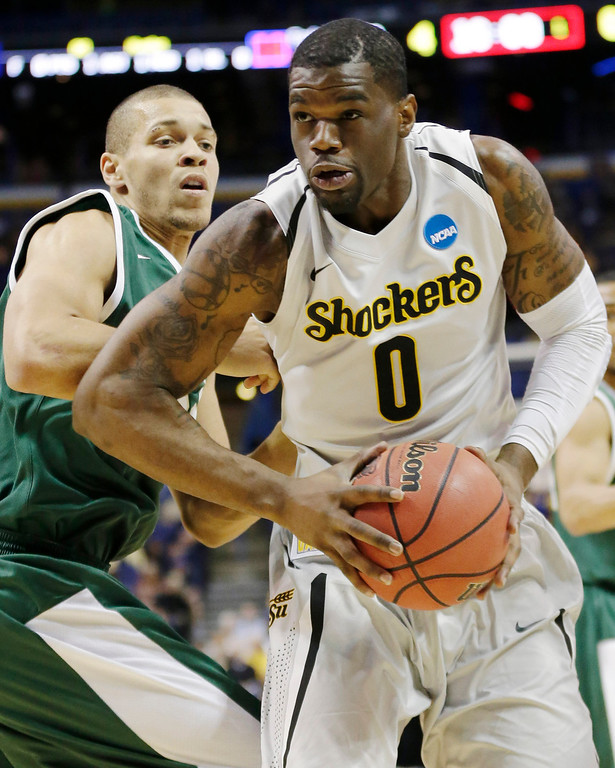 . Wichita State forward Chadrack Lufile (0) takes the ball past Cal Poly forward Chris Eversley (33) during the first half of a second-round game in the NCAA college basketball tournament Friday, March 21, 2014, in St. Louis. (AP Photo/Charlie Riedel)