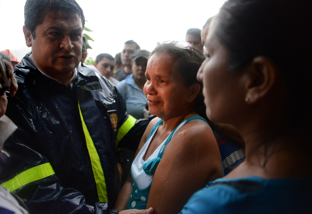 ". Honduran President Juan Orlando Hernandez (L) talks to relatives of some of the at least 11 workers trapped in the San Juan mine, in the Honduran southern department of Choluteca, on July 3, 2014 a day after the gold mine collapsed. Rescuers in Honduras said there were signs of life Thursday from within the mine as they intensified efforts to save them. Using sound detection equipment lowered into the unlicensed mine, ""we\'ve received signals, sounds in the part of the mine where the workers are trapped,\"" Moises Alvarado, head of the national emergency authority, told local radio. The cave-in on Wednesday struck the mine at a depth of 80 meters (260 feet) near the southern town of El Corpus. Rescuers cannot use machinery to try to get to the miners because the ground is unstable. (ORLANDO SIERRA/AFP/Getty Images)"