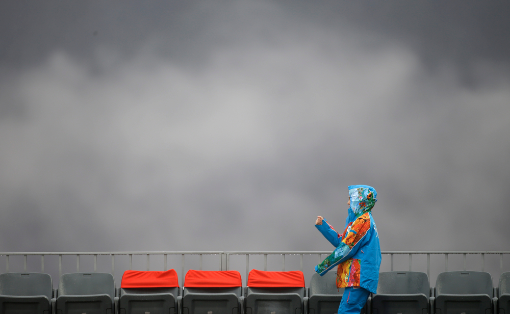 . A volunteer walks through the rain prior to the Nordic combined individual Gundersen large hill competition at the 2014 Winter Olympics, Tuesday, Feb. 18, 2014, in Krasnaya Polyana, Russia. (AP Photo/Gregorio Borgia)
