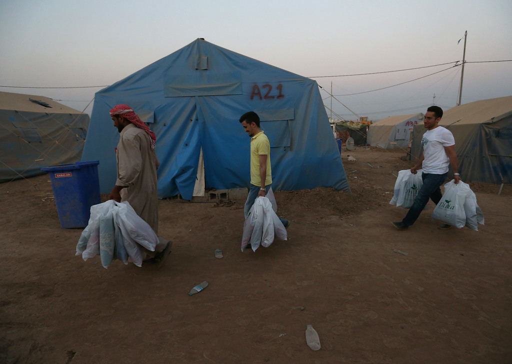 . An Iraqi displaced man, left, helps two Kurdish volunteers from a local charity organization as they carrying bags with copies of the Quran, Islam\'s holy book and carpets prayer to be distributed a day before the starting of the Islamic holy month of Ramadan, at a camp for displaced Iraqis who fled from Mosul and other towns, at a camp for displaced Iraqis who fled from Mosul and other towns, in Khazer area outside Irbil north Iraq, Saturday, June 28, 2014. Across a wide belt that stretches halfway around the globe, the worldís estimated 1.6 billion Muslims will mark the beginning of Ramadan this weekend. The holy season is marred by unprecedented turmoil, violence and sectarian hatreds that threaten to rip apart the Middle East, the epicenter of Islam. (AP Photo/Hussein Malla)
