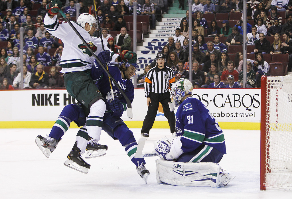 . Nino Niederreiter #22 of the Minnesota Wild collides with Chris Tanev #8 of the Vancouver Canucks in front of goaltender Eddie Lack #31 during the first period of their NHL game at Rogers Arena on February 28, 2014 in Vancouver, British Columbia, Canada. (Photo by Ben Nelms/Getty Images)