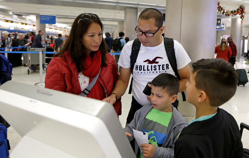 . Passengers Yamile Gomez, left, her spouse Juan Gomez and their children self check in their luggage on their way to Atlanta, to spend the Thanksgiving holiday with their relatives, at Miami International Airport, Wednesday, Nov. 23, 2016, in Miami. Almost 49 million people are expected to travel 50 miles or more for the holiday, the most since 2007, according to AAA.  (AP Photo/Alan Diaz)