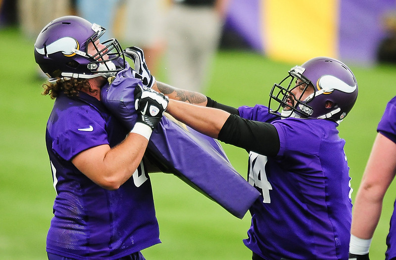 . Minnesota Vikings guard Charlie Johnson, right, stiff arms offensive guard Jeff Baca at Vikings training camp in Mankato, Minn., on Friday, July 26, 2013. (Pioneer Press: Ben Garvin)
