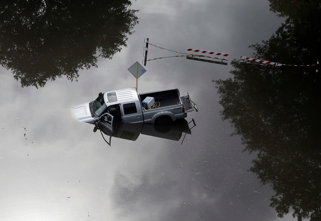 . In this aerial photo, a truck sits in floodwaters near Bear Creek Park Saturday, May 30, 2015, in Houston, Texas. The Colorado River in Wharton and the Brazos and San Jacinto rivers near Houston are the main focus of concern as floodwaters moved from North and Central Texas downstream toward the Gulf of Mexico. (AP Photo/David J. Phillip)
