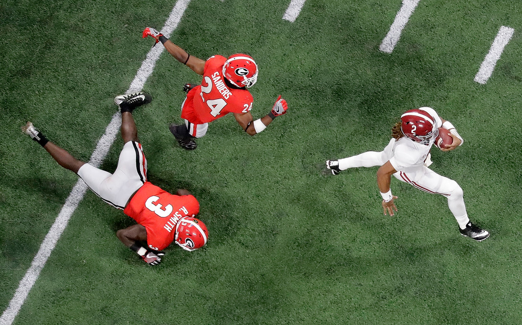 . Alabama quarterback Jalen Hurts runs past Georgia safety Dominick Sanders and Roquan Smith (3) during the first half of the NCAA college football playoff championship game Monday, Jan. 8, 2018, in Atlanta. (AP Photo/John Bazemore)