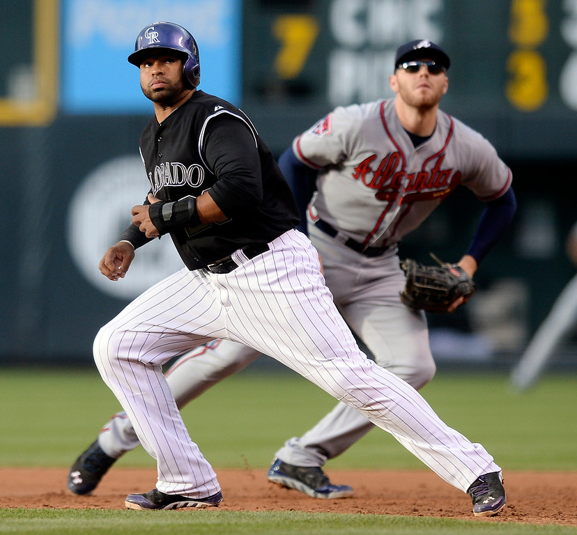 . Colorado baserunner Wilin Rosario and Atlanta first baseman Freddie Freeman leaned in opposite directions at the crack of the bat in the first inning. Freeman chased a foul ball that landed in the stands. The Colorado Rockies hosted the Atlanta Braves Tuesday night, June 10, 2014. (Photo by Karl Gehring/The Denver Post)