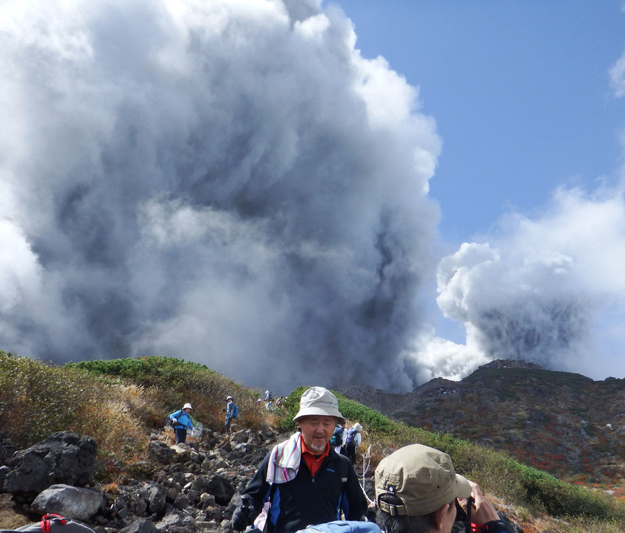 . In this photo taken by an anonymous climber and was offered to Kyodo News, climbers descend Mt. Ontake to flee as the volcanic moutain erupts in central Japan, Saturday, Sept. 27, 2014. With a sound likened to thunder, the 3,067-meter (10,062-foot) mountain spewed large white plumes high into the sky, sending people fleeing, covering surrounding areas in ash, with more than 250 people stuck on the slopes for hours, many taking refuge in mountain lodges that dot the way up. (AP Photo/Kyodo News)