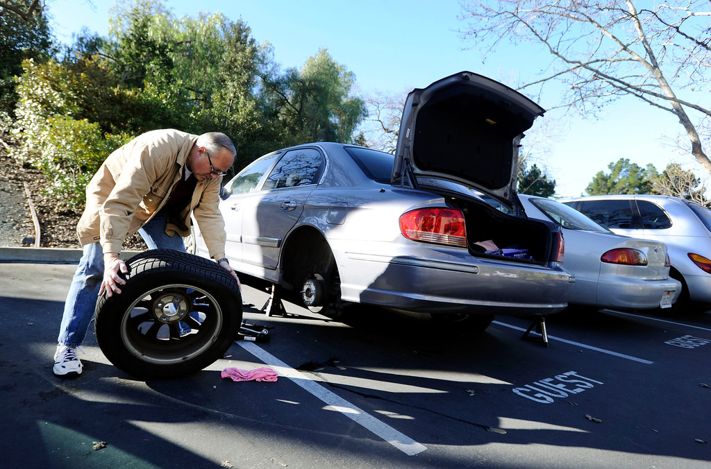 . Dan Zywicki, of Concord, removes the first of four flat tires on his daughter\'s car along Bel Air Drive in Concord, Calif., on Monday, Feb. 11, 2013. Zywicki said his daughter, Kay Zywicki, discovered the flats on Sunday. Concord police reported that tiresd were slashed on about 60 vehicles in the area. (Susan Tripp Pollard/Staff)