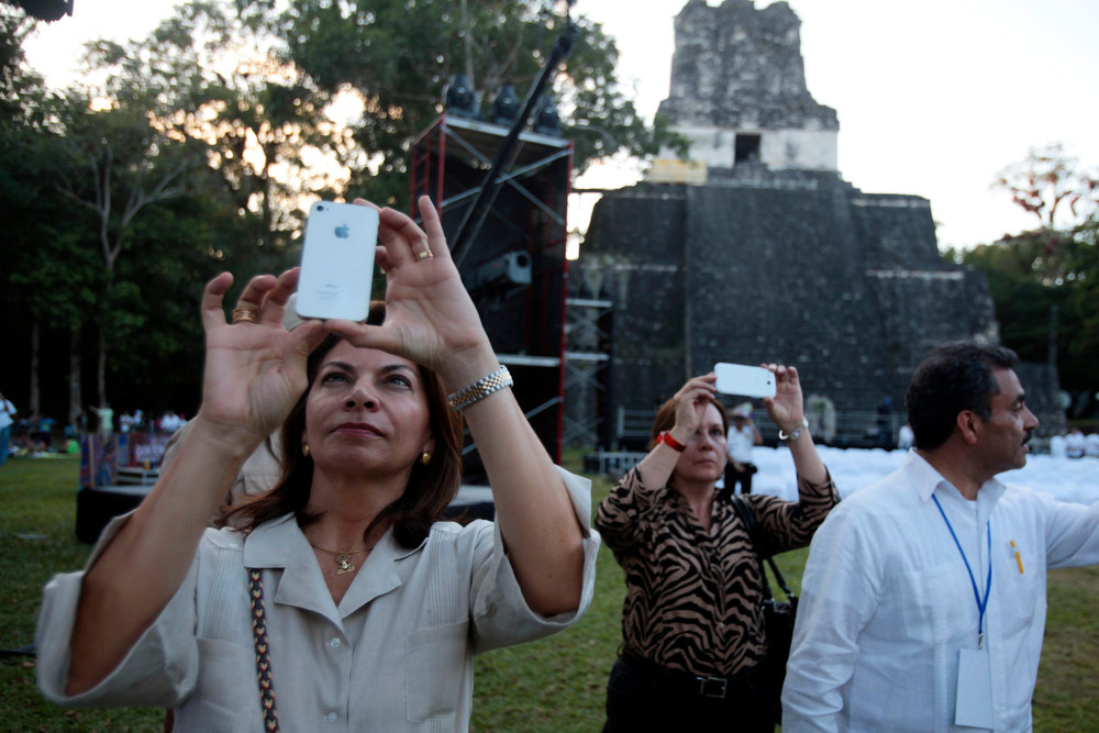 Description of . Costa Rica's President Laura Chinchilla (L) takes photos with her mobile phone a day before the Oxlajuj Baktun celebration at the Tikal Mayan ruins in Peten, Guatemala, December 20, 2012. This week, at sunrise on Friday, December 21, an era closes in the Maya Long Count calendar, an event that has been likened by different groups to the end of days, the start of a new, more spiritual age or a good reason to hang out at old Maya temples across Mexico and Central America.  REUTERS/William Gularte