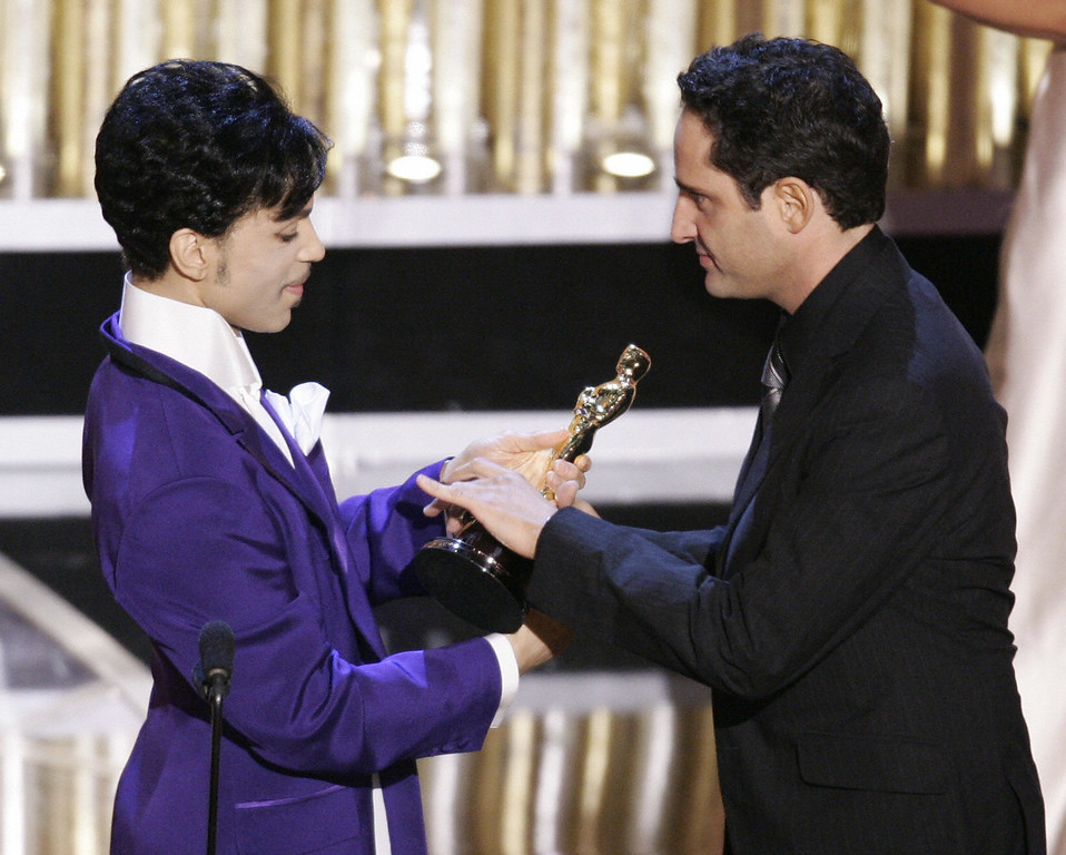". Uruguayan singer Jorge Drexler receives the trophy from musician Prince after ""Al Otro Lado del Rio,\"" won for Best Original Song from \""The Motorcycle Diaries\"" during the 77th Academy Awards show 27 February, 2005, at the Kodak Theater in Hollywood, California. (Photo by TIMOTHY A. CLARY/AFP/Getty Images)"