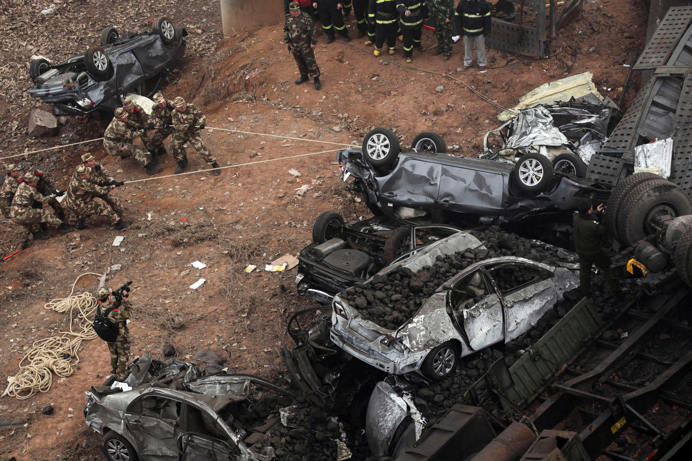 Description of . Chinese paramilitary policemen pull at car wreckage at the accident site where an expressway bridge partially collapsed due to a truck explosion in Mianchi County, Sanmenxia, central China's Henan Province, Thursday, Feb. 1, 2013. A truckload of fireworks intended for Lunar New Year celebrations went off Friday in a massive, deadly explosion that destroyed part of an elevated highway in central China, sending vehicles plummeting 30 meters (about 100 feet) to the ground. (AP Photo)