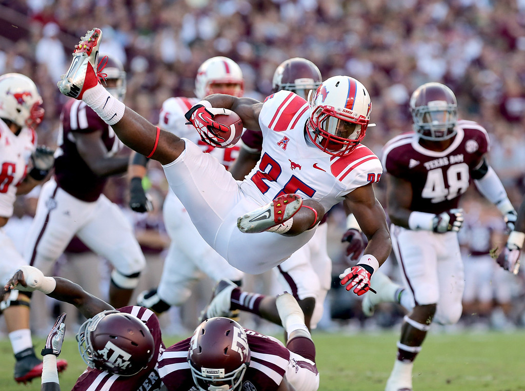 . HOUSTON, TX- SEPTEMBER 21: K.C. Nlemchi #25 of the Southern Methodist Mustangs flies though the air after being hit by the Texas A&M Aggies in the first half on September 21, 2013 at Kyle Field in College Station, Texas. (Photo by Thomas B. Shea/Getty Images)