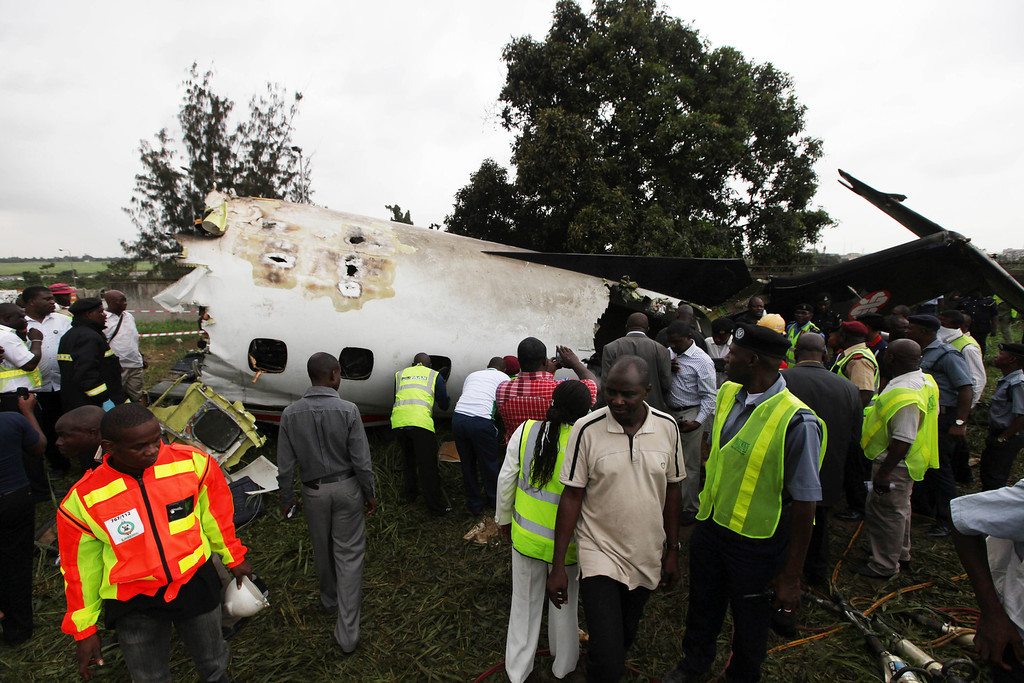 . Rescue workers gather around the wreckage of a charter passenger jet which crashed soon after take off from Lagos airport, Nigeria, Thursday, Oct. 3, 2013. (AP Photo/Sunday Alamba)