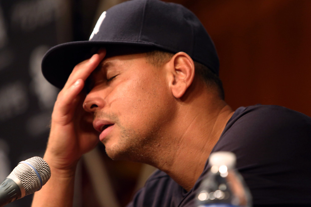 . New York Yankees\' Alex Rodriguez, with his hand to his head, talks during a news conference before the Yankees play the Chicago White Sox in a baseball game at US Cellular Field in Chicago on Monday, Aug. 5, 2013. Rodriguez was suspended through 2014 and All-Stars Nelson Cruz, Jhonny Peralta and Everth Cabrera were banned 50 games apiece Monday when Major League Baseball disciplined 13 players in a drug case, the most sweeping punishment since the Black Sox scandal nearly a century ago. (AP Photo/Charles Cherney)