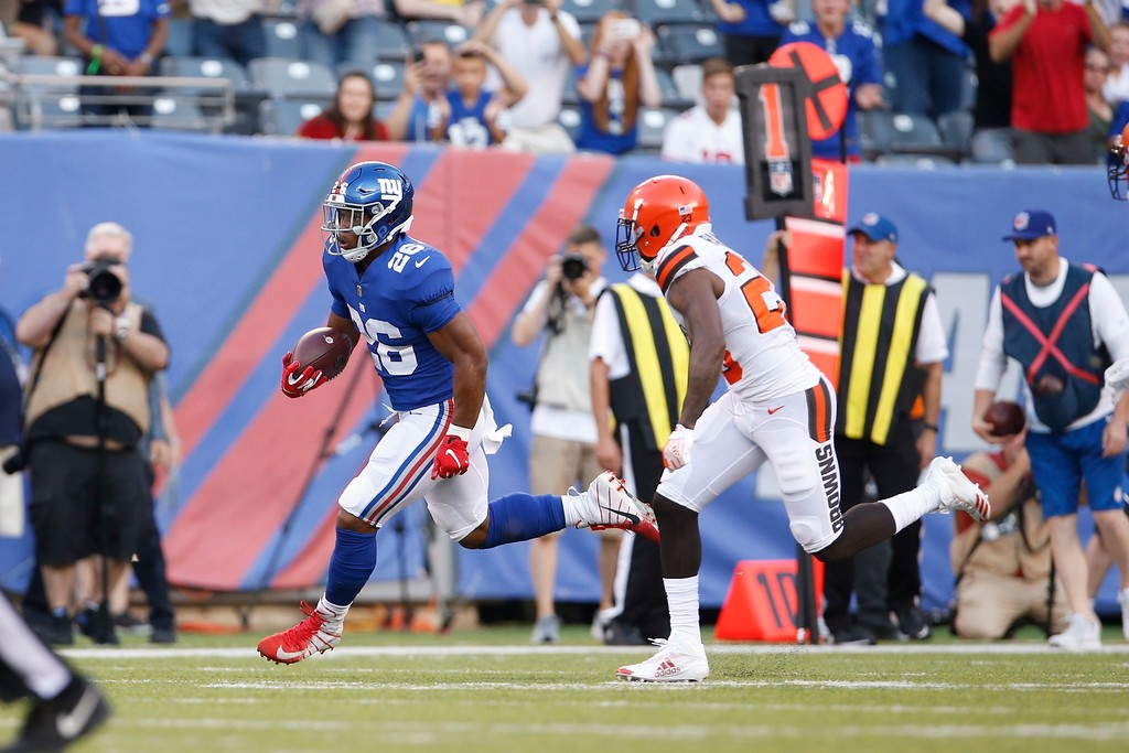 . New York Giants running back Saquon Barkley (26) runs past Cleveland Browns\' Jabrill Peppers (22) during the first half of a preseason NFL football game Thursday, Aug. 9, 2018, in East Rutherford, N.J. (AP Photo/Adam Hunger)