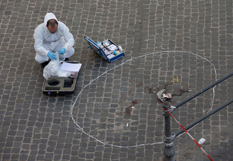 . Forensic police collect evidence where a shooting took place outside Chigi Palace, premier\'s office, in Rome, Sunday, April 28, 2013. Two Italian paramilitary policemen were shot and wounded Sunday in a crowded square outside the premier\'s office in Rome as Italy\'s new leader Enrico Letta was being sworn in at the Quirinal presidential office, about a kilometer (half-mile) away. It was not immediately clear if there was any connection between the shooting and the swearing-in. (AP Photo/Alessandra Tarantino)