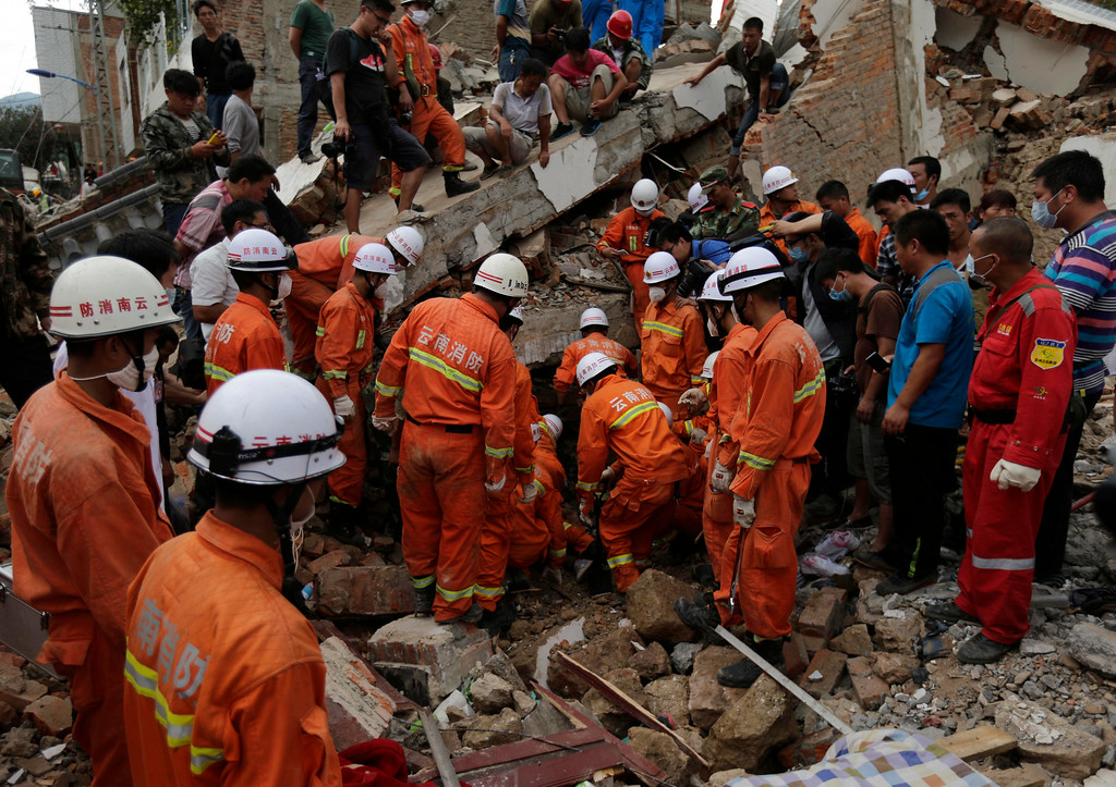 . Rescuers try to retrieve a trapped victim\'s body from a collapsed house following a massive earthquake in the town of Longtoushan in Ludian County in southwest China\'s Yunnan Province Tuesday, Aug. 5, 2014. (AP Photo/Andy Wong)