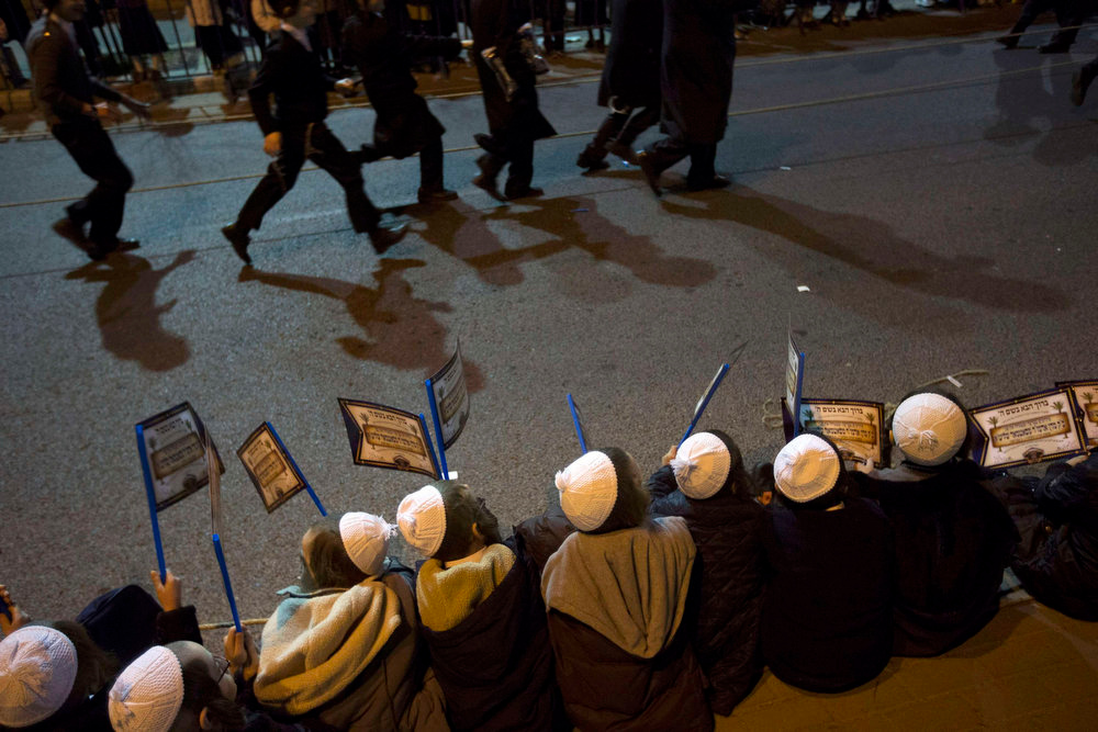 . Ultra-Orthodox Jewish boys hold flags during a rally organised to welcome Rabbi Zalman Leib Teitelbaum, in Jerusalem\'s Mea Shearim neighbourhood January 20, 2013. Local media said that Rabbi Zalman Leib Teitelbaum, son of the late Rabbi Moses Teitelbaum, leader of the Satmar Hasidim landed in Israel on Sunday for the wedding of his granddaughter which will take place later in the week. REUTERS/Ronen Zvulun