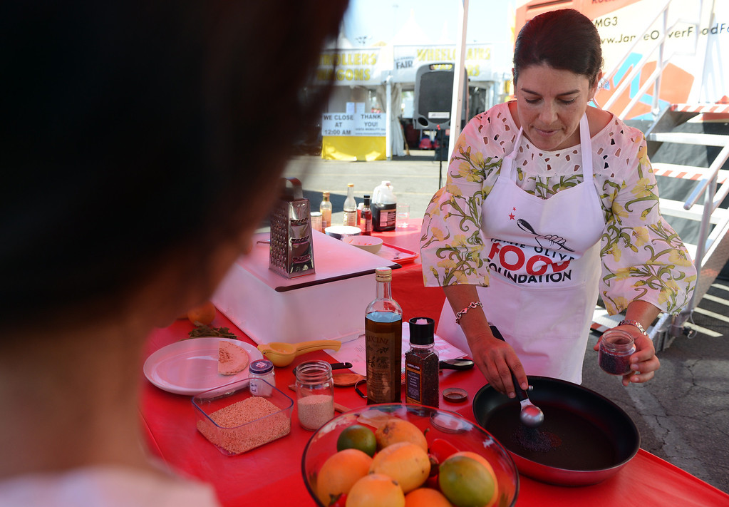 """. Program Trainer Lisa Fontanesi shows kids how to make quick easy snacks outside the Jamie Oliver Food Foundation\'s \""""Big Rig Teaching Kitchen\"""" at the L.A. County Fair at Fairplex in Pomona. (Jennifer Cappuccio Maher/Inland Valley Daily Bulletin)"""